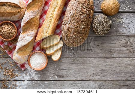 Fresh bread background, top view with copy space. Homemade baguette loaves on rustic wood