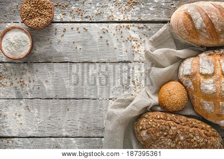 Bread frame on rustic wood background, copy space. Brown and white loaves and flour still life composition with wheat flour sprinkled around.