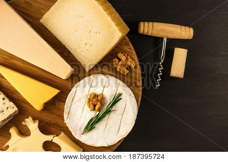 An overhead photo of a selection of cheeses, shot from above on a black texture, with a wine corkscrew and a cork, and a place for text