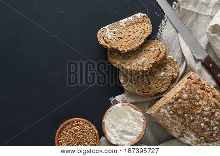 Bakery background, rye bread on black. Flour and grain with copy space