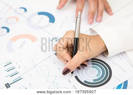 Businesswoman hand with pen writing on graph