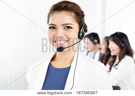 Smiling woman wearing microphone headset as an operator telemarketer call center or customer service staff