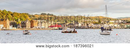 OBAN ARGYLL SCOTLAND - SEPTEMBER 24 2014: waterfront and bay in a bright sunny summer sunset. This harbour is the gateway to Mull and the islands as well as fishermen base for seafood captures.