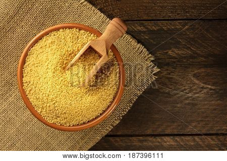 A bowl of raw couscous with a scoop, shot from above on dark rustic textures with a place for text