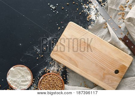 Baking background, flour and cutting board at black. Bakery and home bread making concept. Copy space