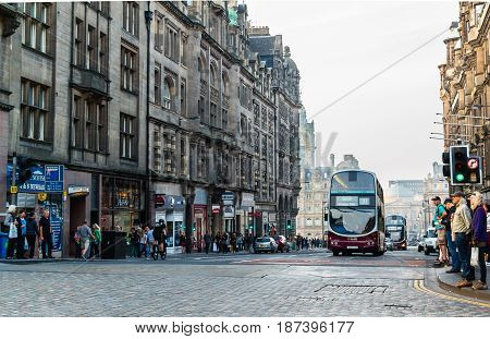 EDINBURGH SCOTLAND - SEPTEMBER 13 2014: Lothian Buses' double decker bus on a crowded North Bridge street while pedestrians wait for a green traffic light to cross the paved street.