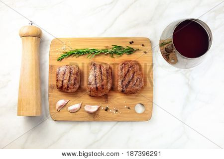 Three slices of grilled meat, beef fillets, shot from above on a wooden board with a sprig of rosemary, garlic cloves, salt, pepper grinder, and a glass of red wine, with a place for text