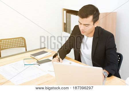 Businessman writing while using laptop computer in the office