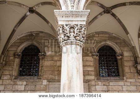 DUBROVNIK CROATIA - JULY 16th 2016: column and gothic arches and windows detail at Sponza Palace front porch located at Stradun street (Placa) ending square in the Old Town.