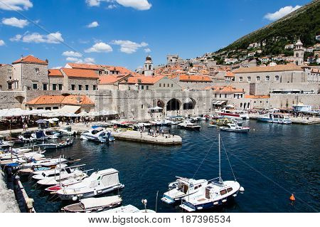 DUBROVNIK CROATIA - JULY 16 2016: leisure boats docked at the Old Port surrounded by Old Town's antique stone buildings in a sunny summer day. The former Arsenal now houses a restaurant for tourists