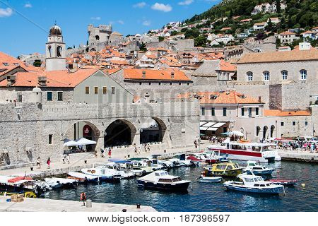 DUBROVNIK CROATIA - JULY 19 2016: closeup of Old Port and arsenal with Old Town as background in a sunny summer day. Mediterranean sea and beautiful islands are an attraction in the Croatian coast.