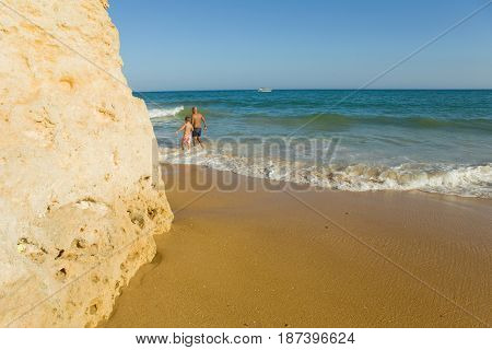 ALBUFEIRA, PORTUGAL - AUGUST 22, 2016: People at the famous beach of Olhos de Agua in Albufeira. This beach is a part of famous tourist region of Algarve.