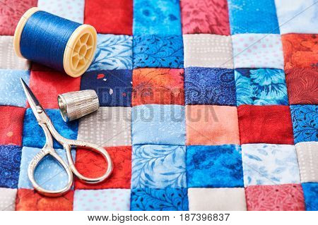Scissors thread and thimble lying on blue and red square pieces of fabric sewn together