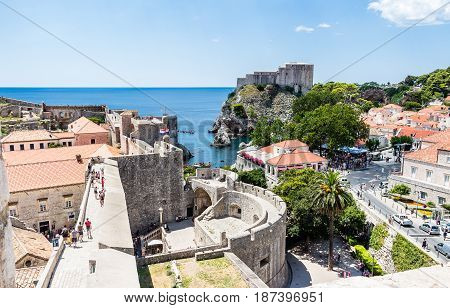 DUBROVNIK CROATIA - JULY 19th 2016: Pile Gate and Fort Lovrijenac guarding Old Town entrance at city walls. This touristic location opens to rocky sea cove in calm and blue Mediterranean sea.
