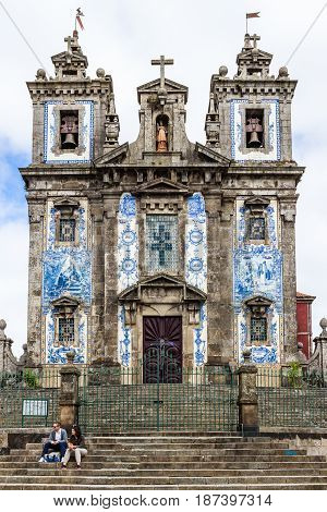 PORTO PORTUGAL - MARCH 11 2017: Saint Ildefonso church tiled facade at the city old town with tourists sitting on the staircase. The painted enameled azulejos are an element of Portuguese culture.
