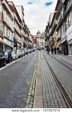PORTO PORTUGAL - MARCH 11 2017: Saint Ildefonso church uphill of Rua 31 de Janeiro at the city old town. The cobblestone steep street still has the old tramway rails.