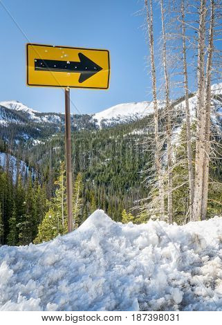 arrow road sign with bullet holes in mountain winter scenery