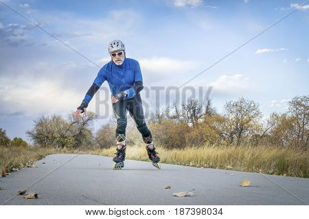 Senior athletic male  inline skating on the Poudre RIver Trail in Colorado, late fall scenery