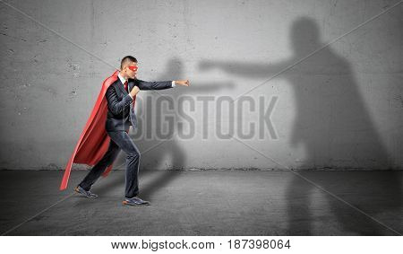 A businessman in a red cape and a mask fighting off a shadow of another bigger man on concrete background. Uneven competition. Hidden adversary. Uneven business conditions.