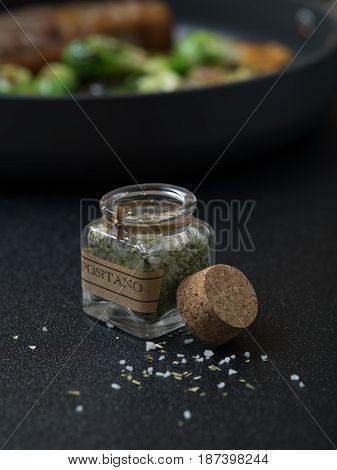 close up view of small bottle with Italian seasoning on gray background