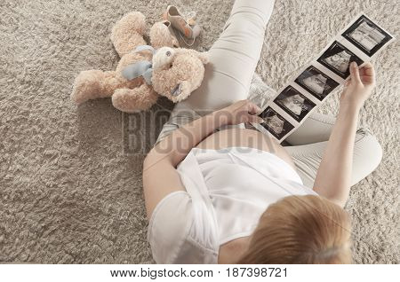 Pregnant woman looking at ultrasonography images - expecting a baby concept