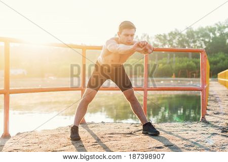 Young sporty man bending forward and doing stretching exercise