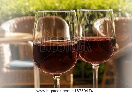 Two glasses of red wine on a sunlit terrace, on a blurred background of rattan chairs and green plants. Selective focus