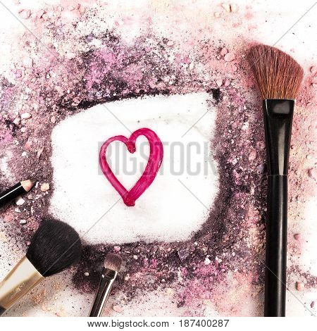 A square photo of makeup brushes, pencil and lip gloss on white marble background, with traces of powder and blush forming a frame with a heart in it. Love Makeup valentine design