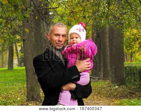 dad in the black coat holds daughter on hands in autumn Park