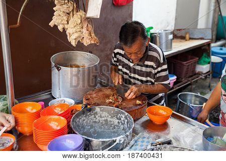 Man Cuts Pork For Rice Porridge