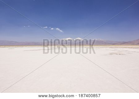 saline of laguna rossa in atacama desert surrounded by high peaks of tres cruses mountain in chile