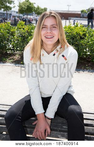 Blond Teenage Girl In Front Of City Skatepark