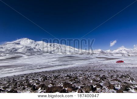 red car near highest chilean snow-covered volcano ojos del salado in chile