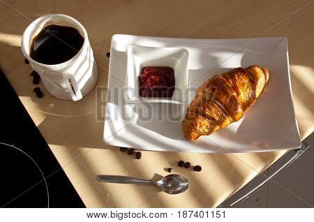 Coffee croissant and jam - french breakfast in the morning sun