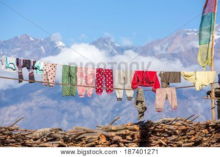Drying laundry on the roof of nepalese brick house with mountains background