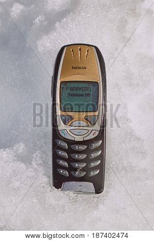 ALPE D'HUEZ, FRANCE - MARCH 14, 2017: Nokia 6310i cellphone laying in the snow. The 6310i was a very popular corporate phone after its introduction in 2002