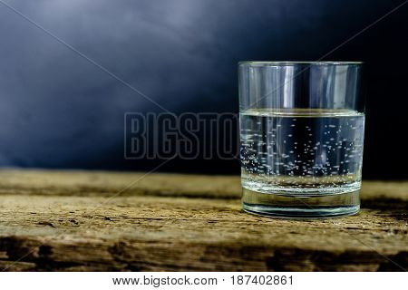 Glass with water on a wooden table on a dark background.