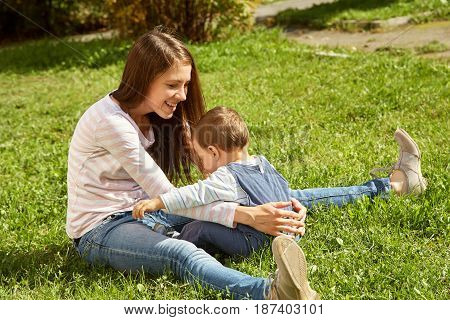 young mother playing with her baby. Mom and son sitting on the grass in a park