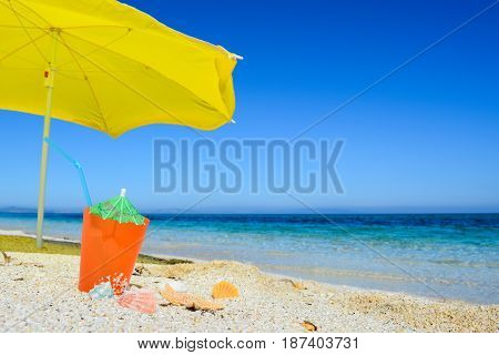 Yellow parasol and orange drink on the beach