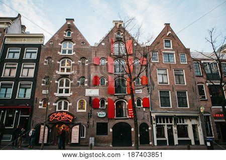 Amsterdam, The Netherlands, January 2, 2017: Houses on the red light street in Amsterdam. A well-known street in the whole world with legal prostitution and sex theaters and erotic nightclubs.