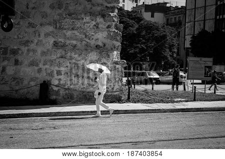 Havana, Cuba - June 30, 2012; member of Santeria Cuban religious sect dressed in all white with umbrella contrasts with rough surrounds as he walks along city street past old stone building Havana.