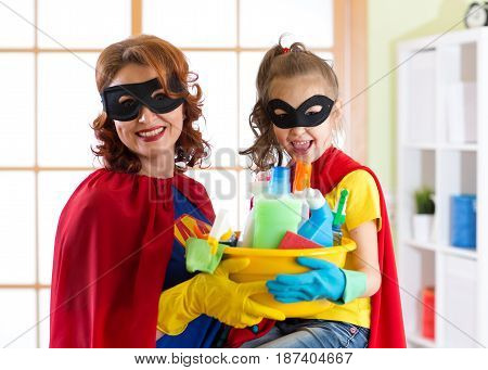 Mother and her child in Superhero costume. Mom and kid ready to house cleaning. Houseworking and housekeeping.