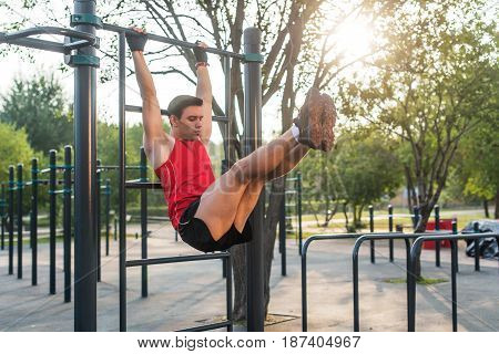 Fitnes man hanging on wall bars performing legs raises. Core cross training working out abs muscles.