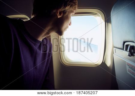 young man sitting at the window of the plane. traveler in the airplane
