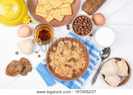 Top view of healthy breakfast for kids. Oat cereal granola in bowl on white wooden background