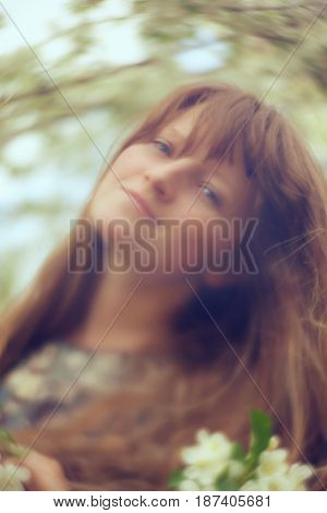 photo with artistic blurring and blur effect. special defocused effect. vintage toning. film retro style. outdoor portrait of a young beautiful woman. spring flowers