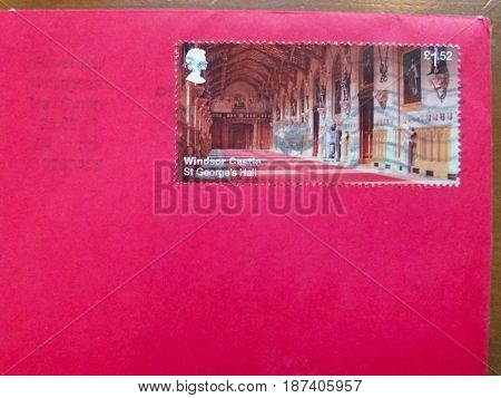 LONDON UK - CIRCA FEBRUARY 2017: 1.52 GBP Royal Mail stamp showing Windsor Castle St George's hall over a magenta envelope