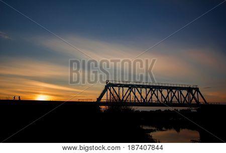 Metal railway bridge over the river at sunset