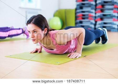 Fit woman doing plank exercise and push ups working on abdominal muscles and triceps