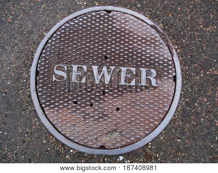 A manhole/sewer cover set into the concrete